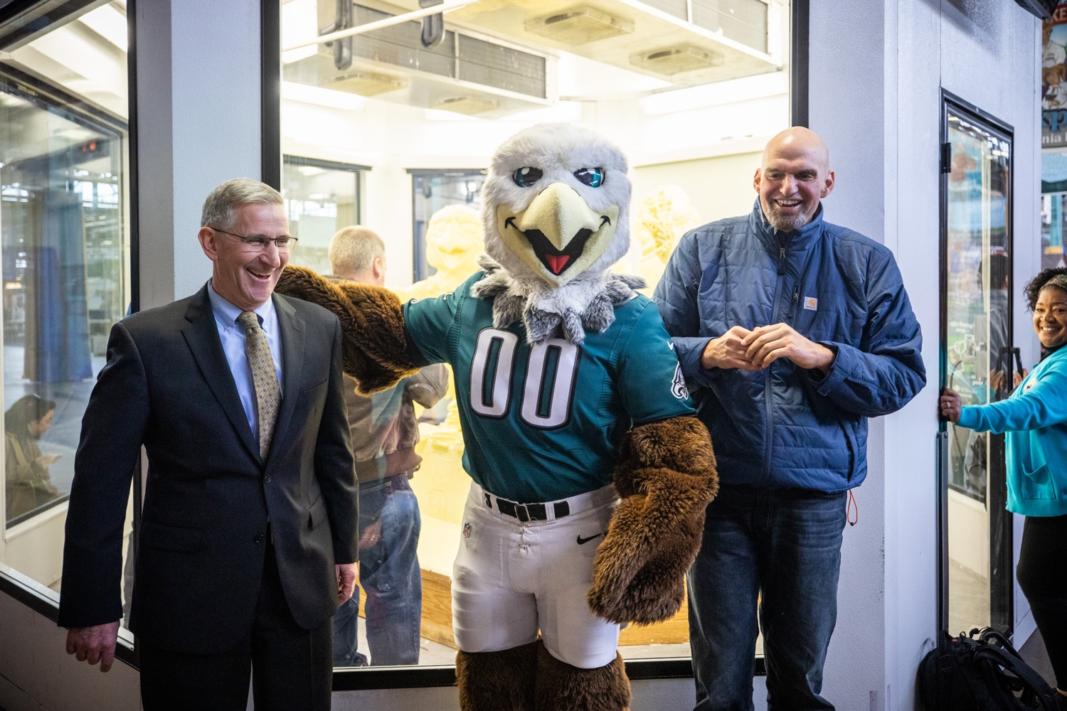"<a href=""http://filesource.abacast.com/commonwealthofpa/photo/17646_agric_butter_sculpture_dz_022.jpg"" target=""_blank"">⇣ Download Photo<br></a>Philadelphia Eagles Swoop, Lt. Governor John Fetterman,  and Secretary of Agriculture Russell Redding at the Pennsylvania Farm Show butter sculpture.  Lt. Governor John Fetterman and Secretary of Agriculture Russell Redding today unveiled the 2020 Pennsylvania Farm Show butter sculpture, carved from a half-ton of butter depicting three of Pennsylvanias beloved professional sports mascots: Philadelphia Flyers Gritty, Philadelphia Eagles Swoop, and Pittsburgh Steelers Steely McBeam celebrating with a spread of Pennsylvania dairy products. The sculpture, a long-time Farm Show staple, encourages Pennsylvanians to be a fan of Pennsylvania dairy and give a cheer to the more than 6,200 dairy farmers in the commonwealth.  Harrisburg, PA  January 2, 2020"
