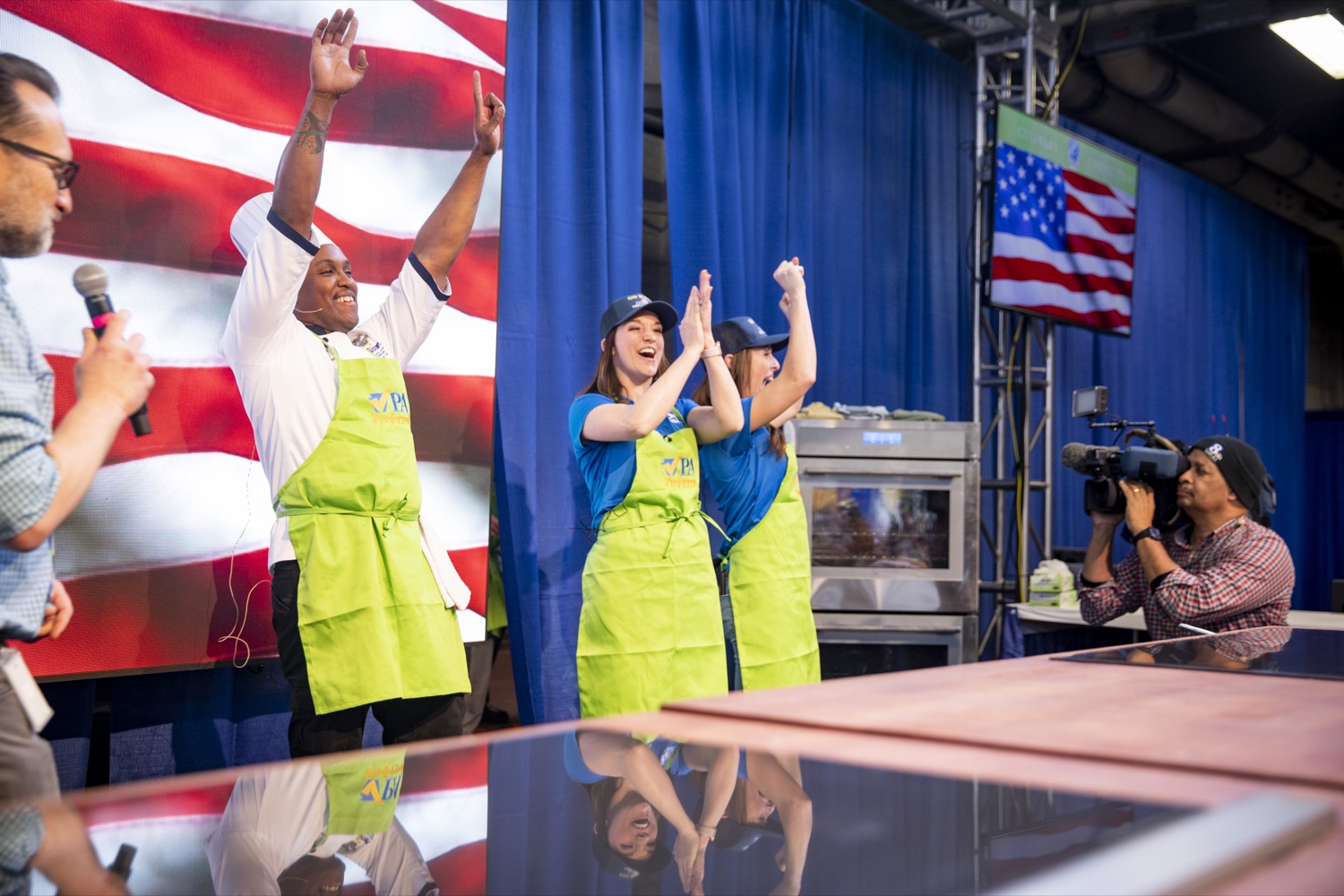 """<a href=""""http://filesource.abacast.com/commonwealthofpa/photo/17651_AGRIC_ARMY_NAVY_COOKOFF_CZ_01.jpg"""" target=""""_blank"""">⇣Download Photo<br></a>Culinary Specialist First Class Marlon ONeil Haughton celebrates his victory with Sous Chefs Corinne Lillis and Shannon Murphy of WGAL Channel 8 at the 2020 Army vs. Navy Cook-Off in Harrisburg on January 9, 2020."""