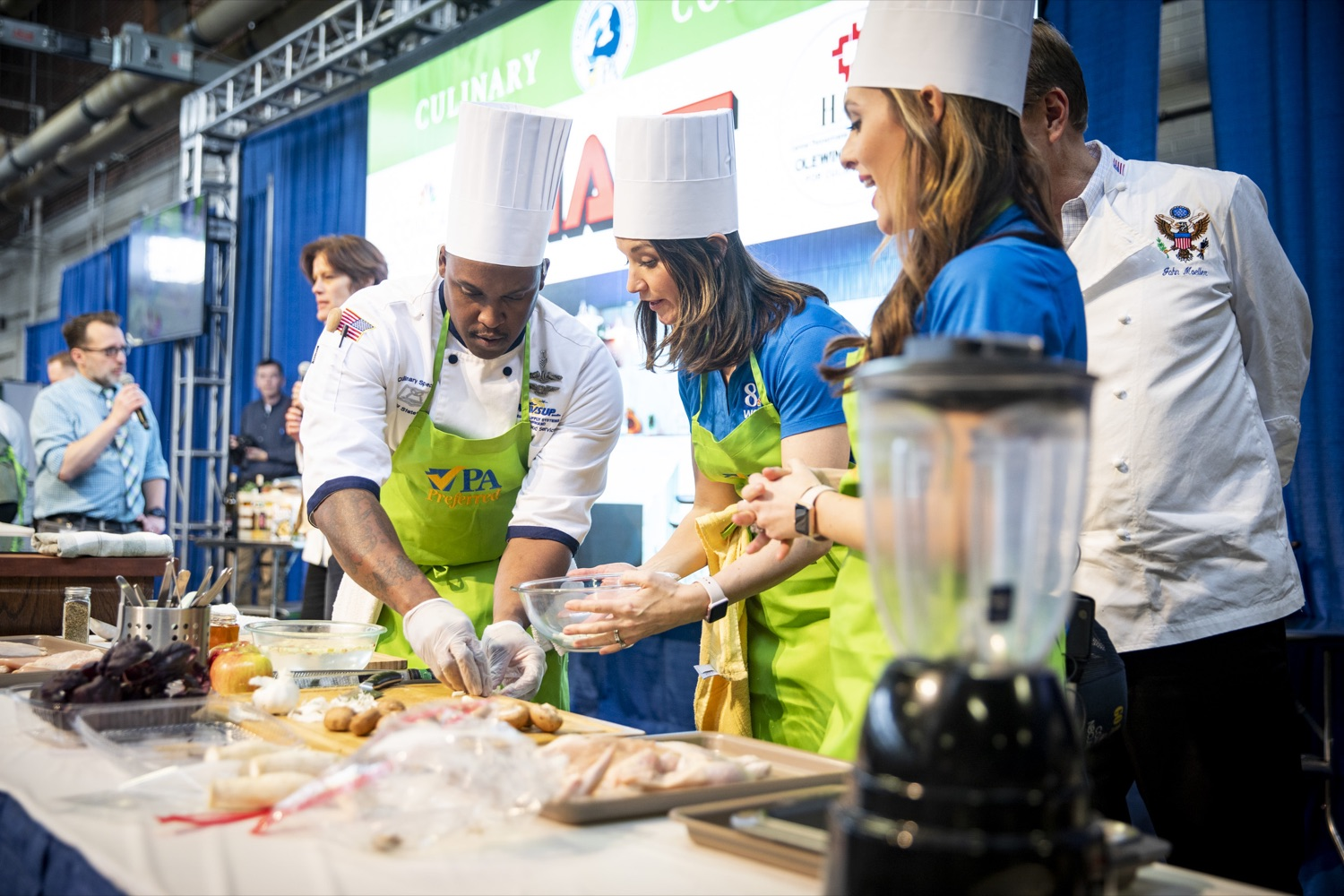 """<a href=""""http://filesource.abacast.com/commonwealthofpa/photo/17651_AGRIC_ARMY_NAVY_COOKOFF_CZ_07.jpg"""" target=""""_blank"""">⇣Download Photo<br></a>Culinary Specialist First Class Marlon ONeil Haughton prepares his meal with Sous Chefs Shannon Murphy and Corinne Lillis of WGAL Channel 8 at the 2020 Army vs. Navy Cook-Off in Harrisburg on January 9, 2020."""