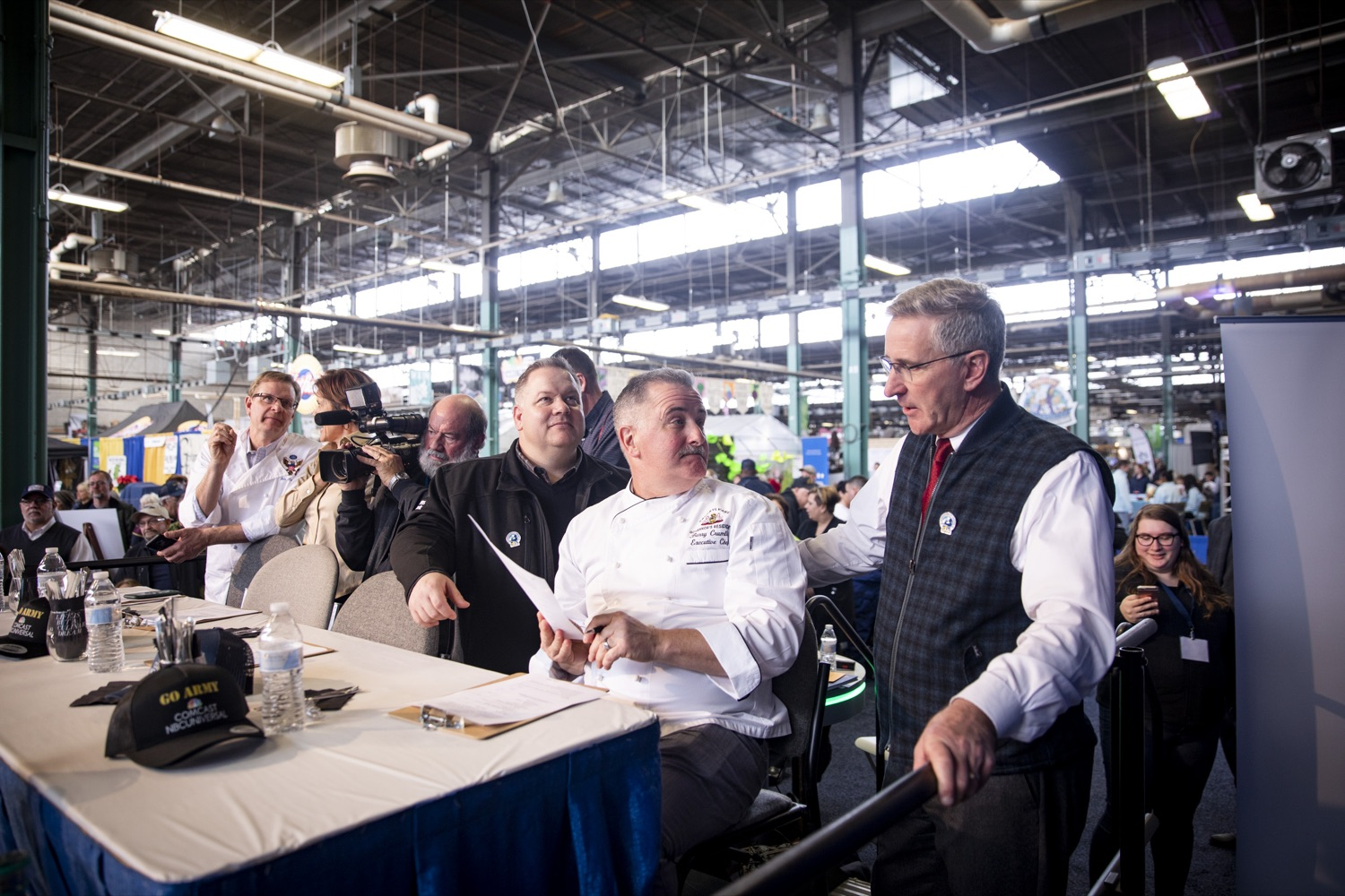 """<a href=""""http://filesource.abacast.com/commonwealthofpa/photo/17651_AGRIC_ARMY_NAVY_COOKOFF_CZ_11.jpg"""" target=""""_blank"""">⇣Download Photo<br></a>Executive Chef at the PA Governors Residence Barry Crumlich shares notes from the judges panel with Secretary Russell Redding at the 2020 Army vs. Navy Cook-Off in Harrisburg on January 9, 2020."""