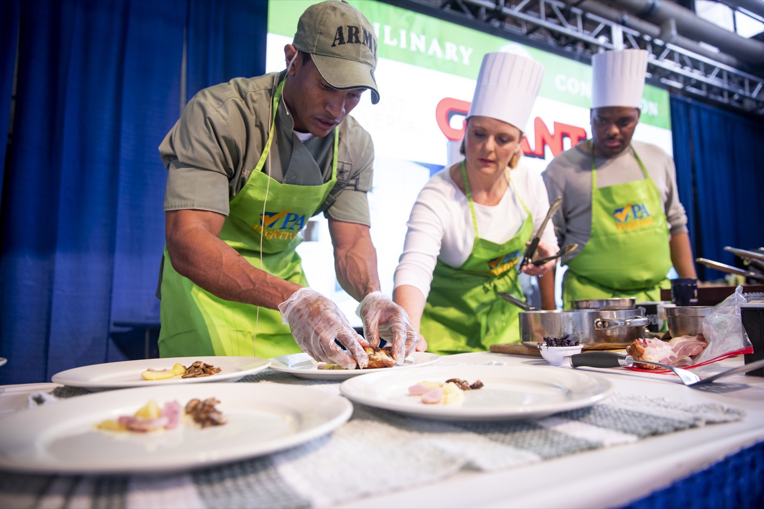 """<a href=""""http://filesource.abacast.com/commonwealthofpa/photo/17651_AGRIC_ARMY_NAVY_COOKOFF_CZ_13.jpg"""" target=""""_blank"""">⇣Download Photo<br></a>Sergeant Pete O. Linton plates his dish with Sous Chefs Ali Lanyon and James Crumble of ABC27 News at the 2020 Army vs. Navy Cook-Off in Harrisburg on January 9, 2020."""