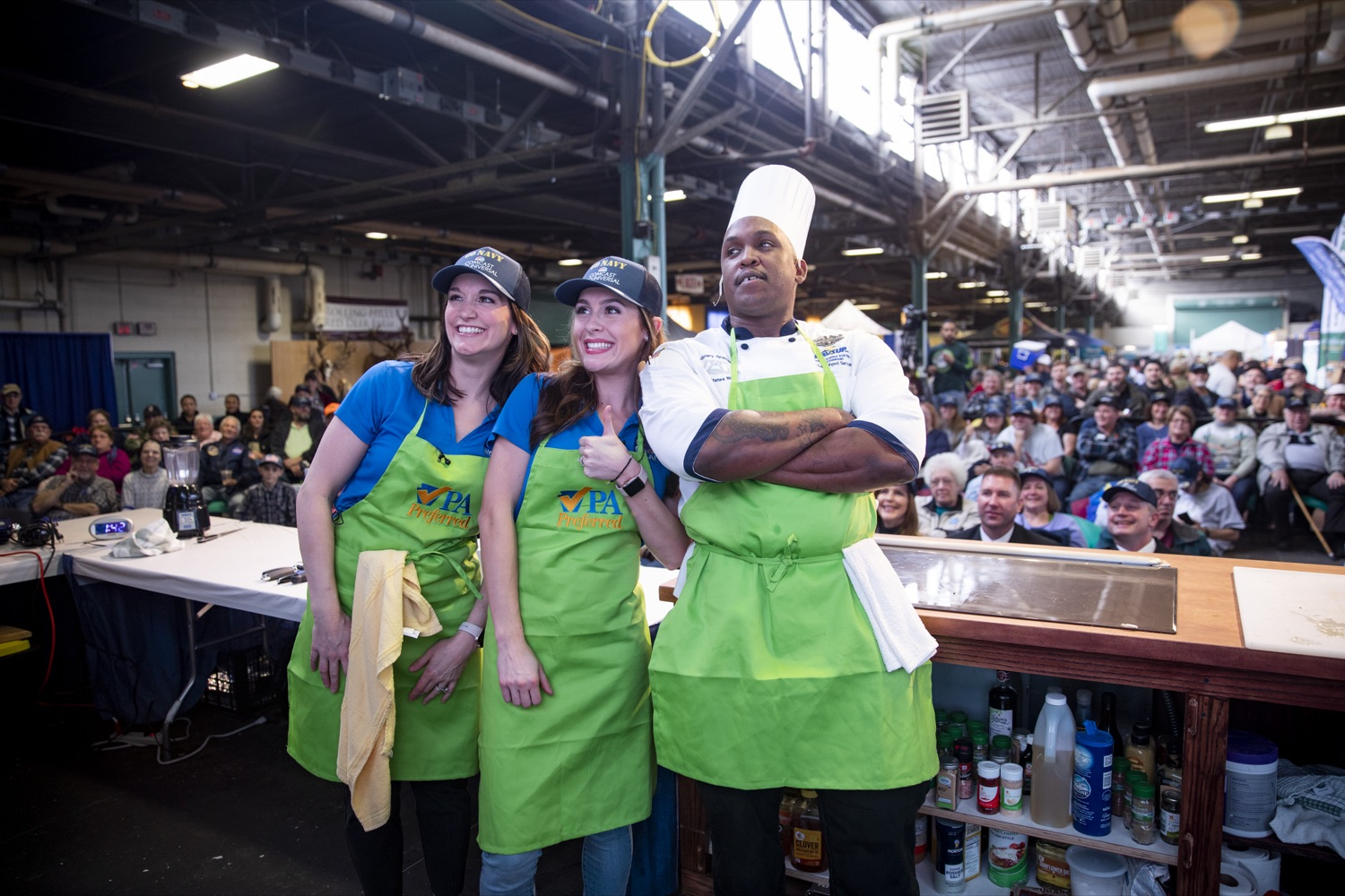 """<a href=""""http://filesource.abacast.com/commonwealthofpa/photo/17651_AGRIC_ARMY_NAVY_COOKOFF_CZ_16.jpg"""" target=""""_blank"""">⇣Download Photo<br></a>Culinary Specialist First Class Marlon ONeil Haughton poses with Sous Chefs Shannon Murphy and Corinne Lillis of WGAL Channel 8 at the 2020 Army vs. Navy Cook-Off in Harrisburg on January 9, 2020."""